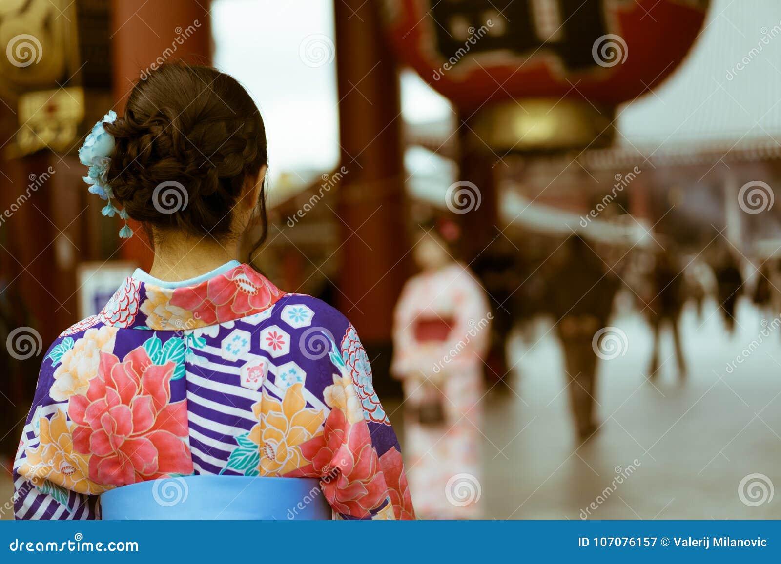 Tradycyjna Japońska kobieta jest ubranym kimono patrzeje wejście Senso-Ji świątynia, Asakusa, Tokio, Japonia