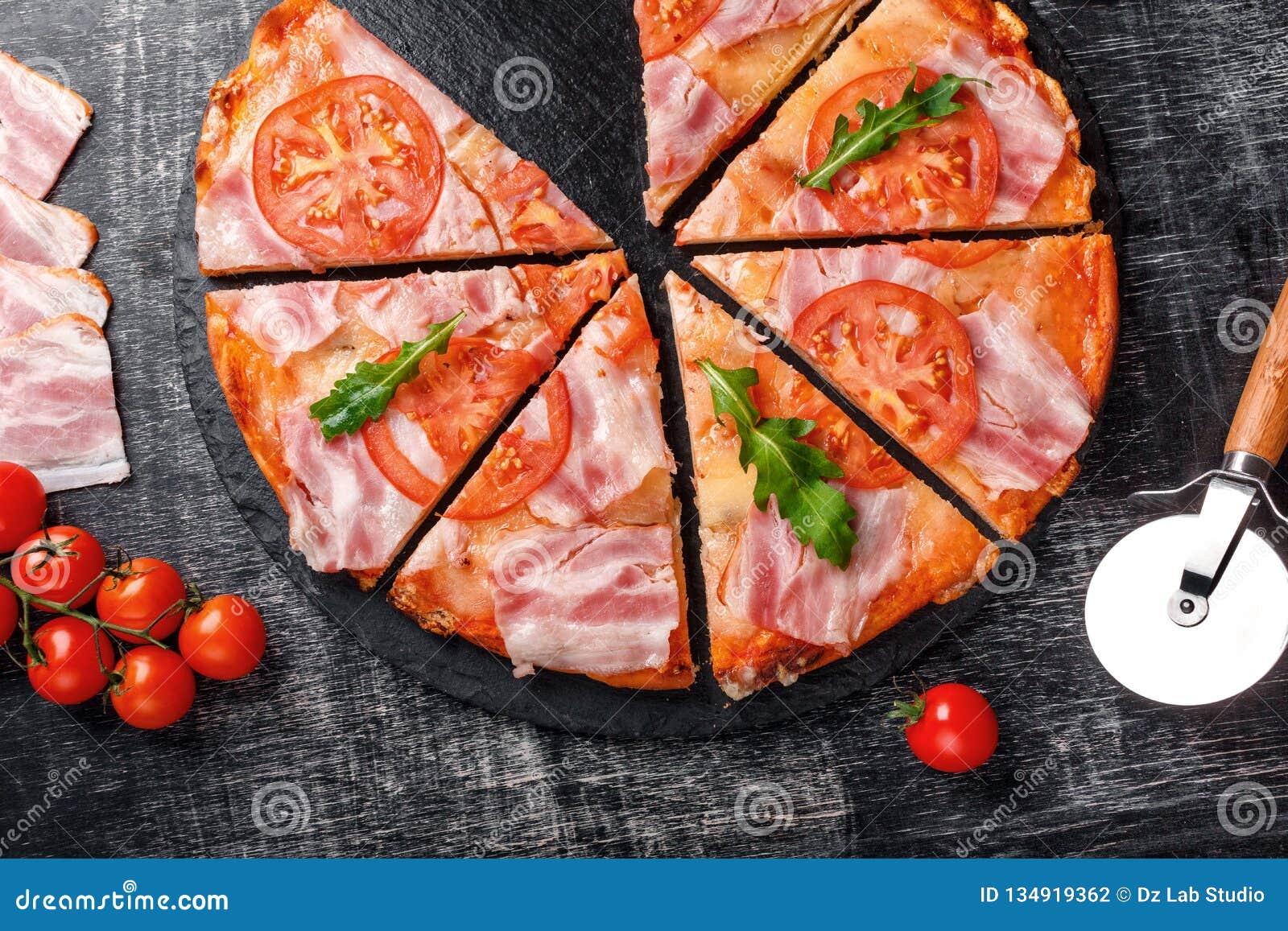 Tradycyjna włoska pizza z mozzarella serem, baleronem, pomidorami, pieprzem, pepperoni pikantność i świeżym rucola,