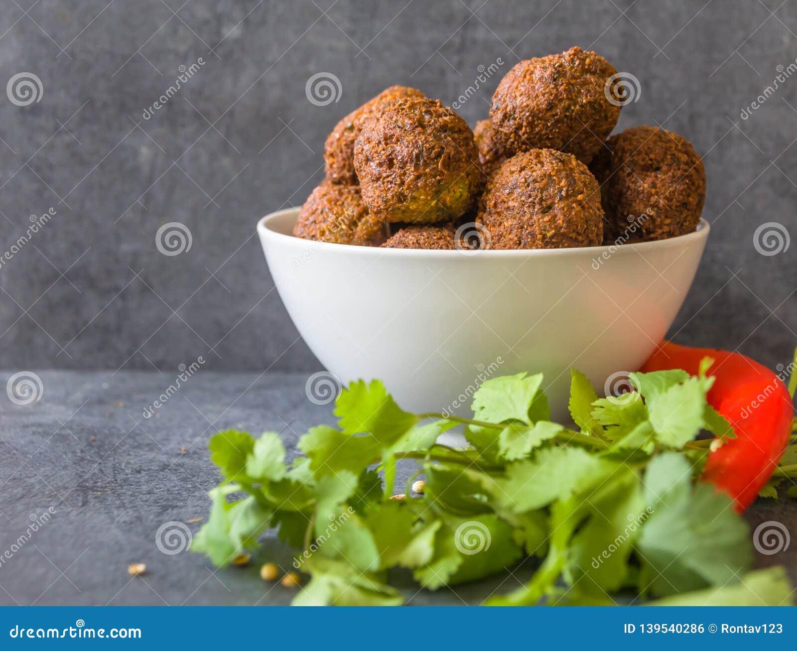 Tradycyjne domowej roboty chickpea Falafel piłki w pucharze z kolenderami opuszczają & ziarna, czerwony pieprz & kapusta, pitta c