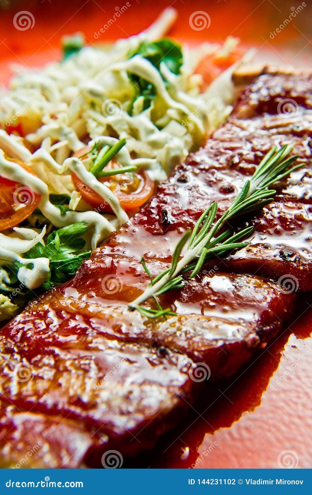 Tradycyjni Amerykańscy grill wieprzowiny ziobro z bocznym naczyniem zielona sałatka Szary tło, boczny widok, w górę