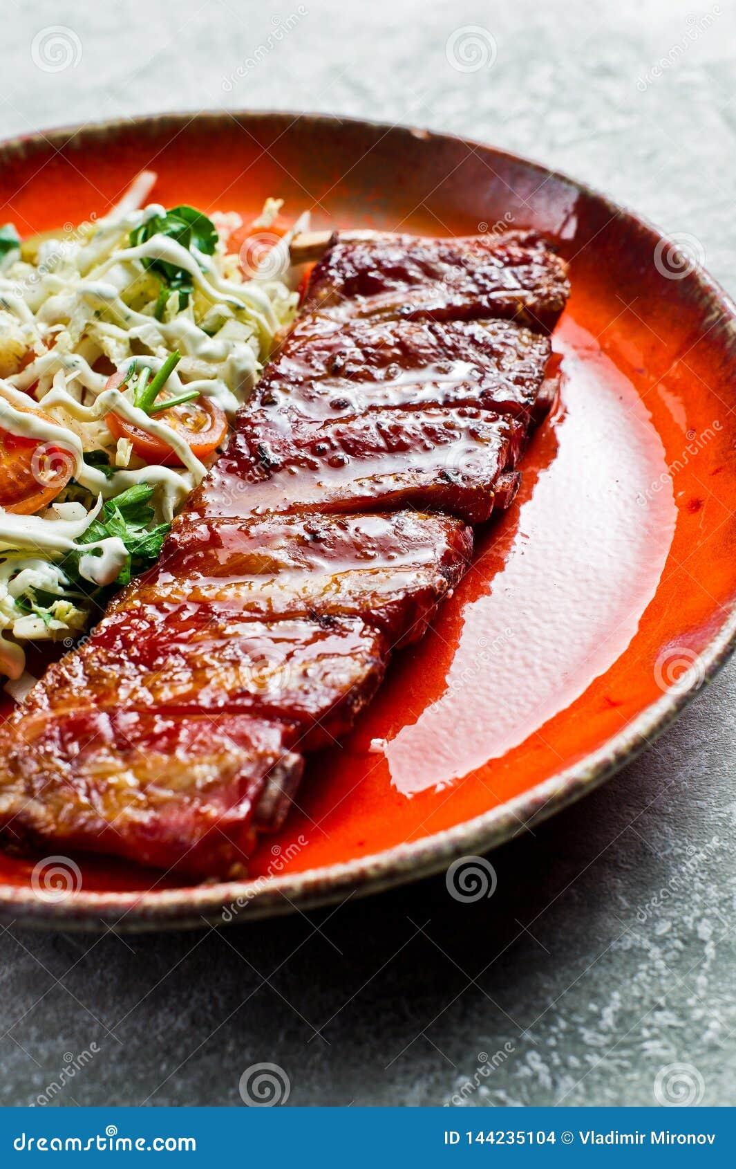 Tradycyjni Ameryka?scy grill wieprzowiny ziobro z bocznym naczyniem zielona sa?atka Popielaty backgroun