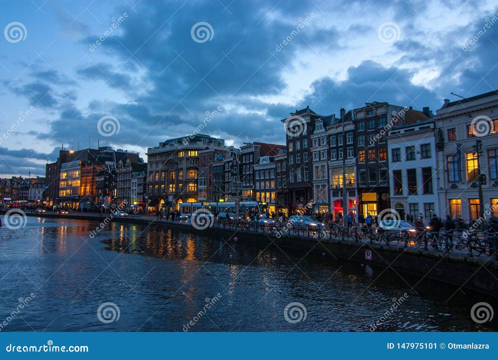 Tradycyjni kanałów domy na Damrak przy półmrokiem w Amsterdam