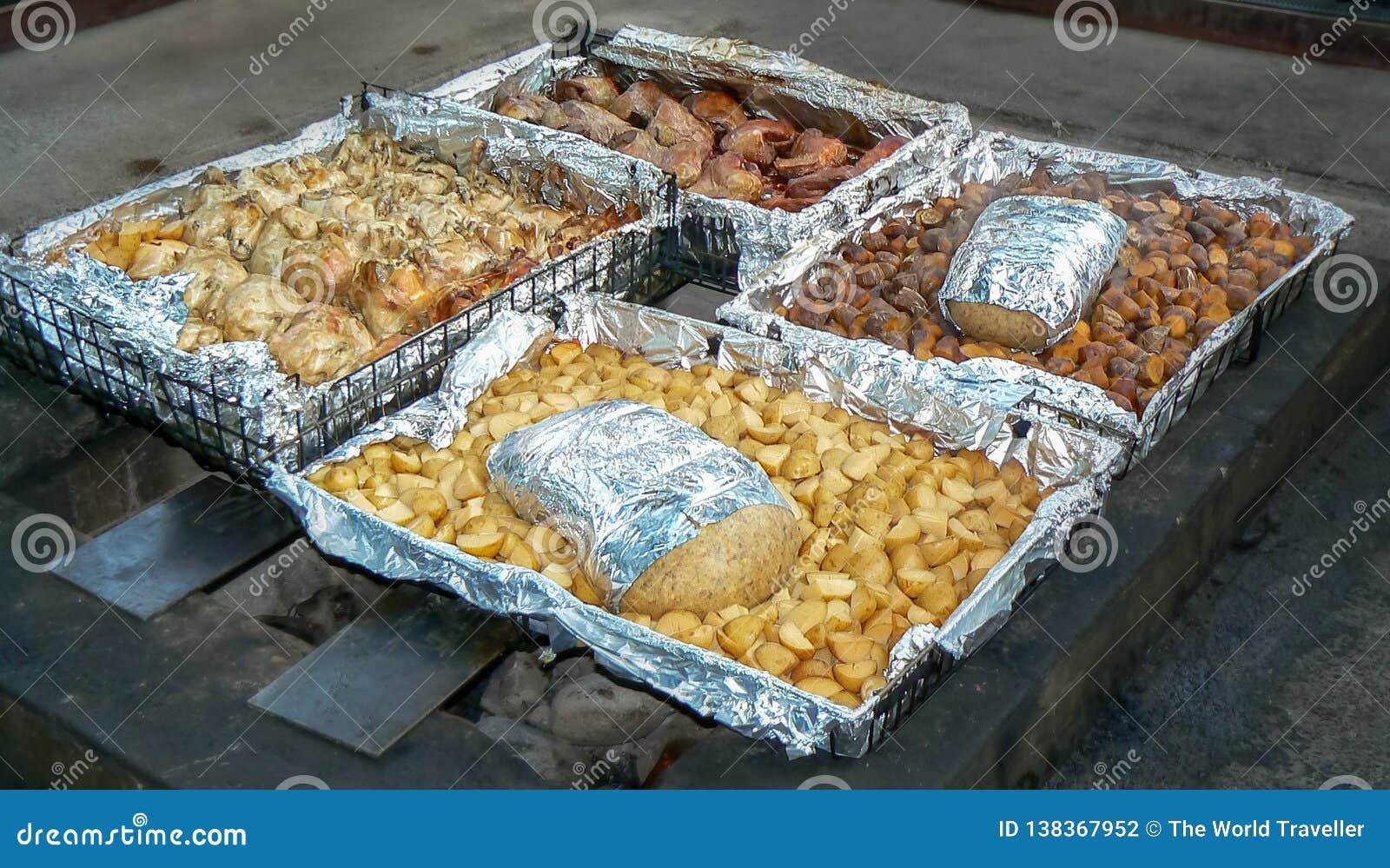 Tradycyjny hangi posiłek, gotujący metro w ziemskim piekarniku Maoryjskimi ludźmi, Rotorua, Północna wyspa, Nowa Zelandia