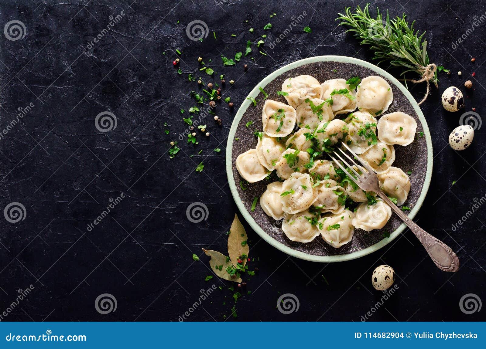 Tradycyjny rosyjski pelmeni, pierożek, kluchy z mięsem na czerni betonuje tło Pietruszka, przepiórek jajka, pieprz