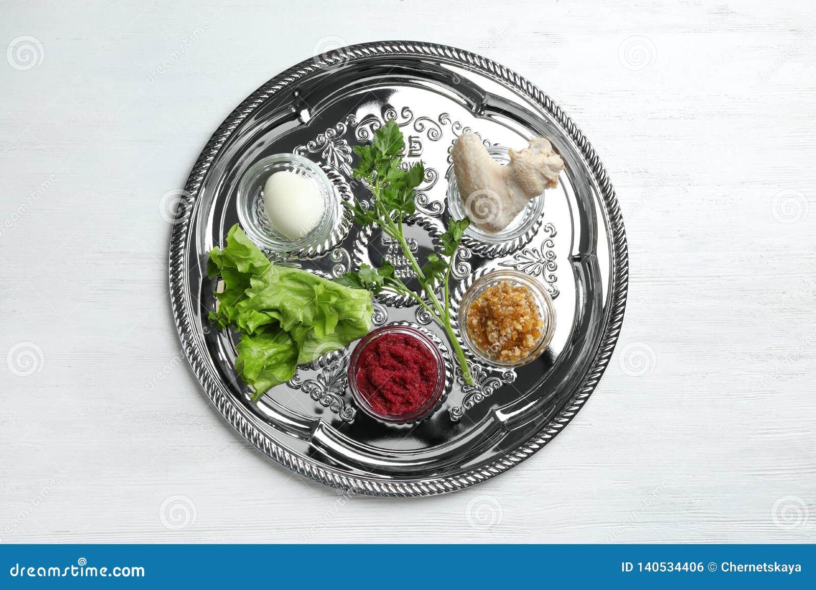 Tradycyjny srebny talerz z symbolicznym posiłkiem dla Passover Pesach Seder na drewnianym tle