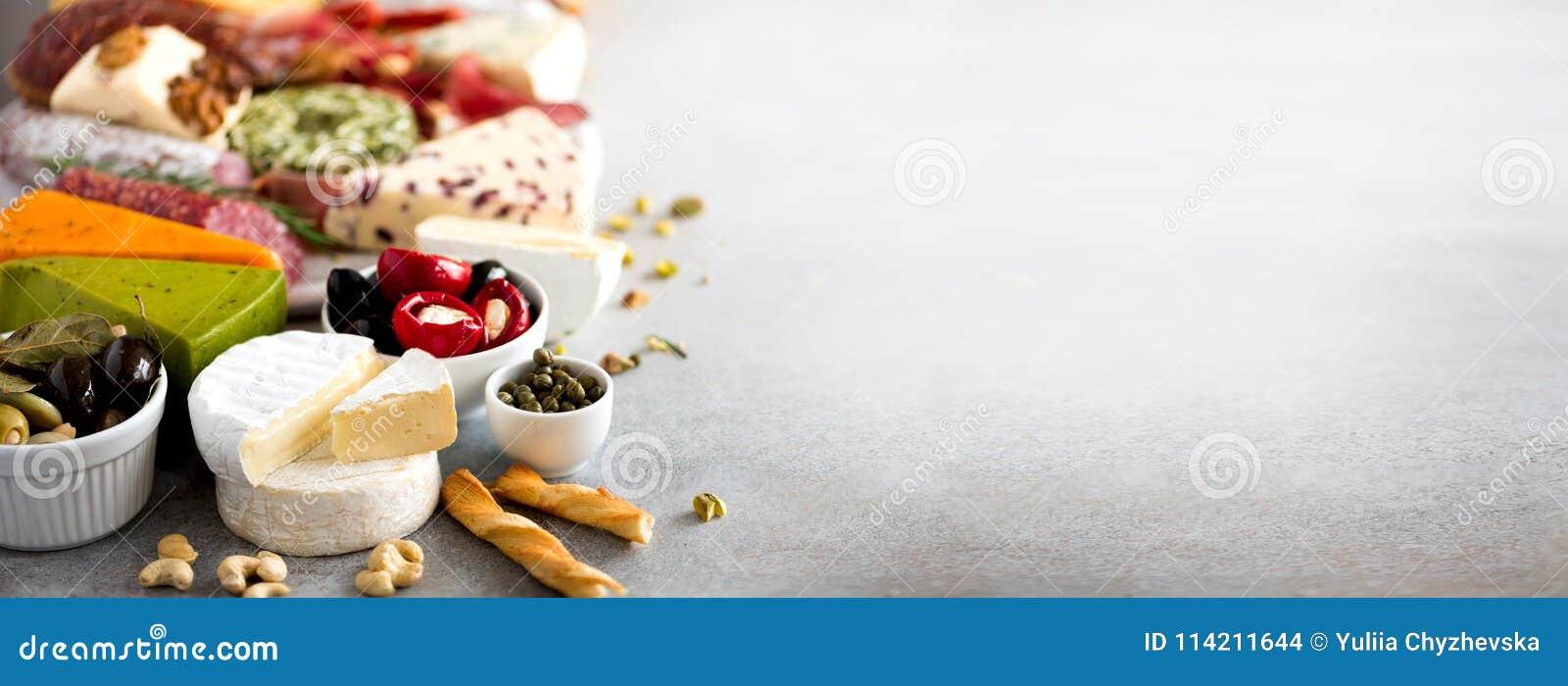 Tradycyjny włoski antipasto, tnąca deska z salami, zimno dymiący mięso, prosciutto, baleron, sery, oliwki, kapary dalej