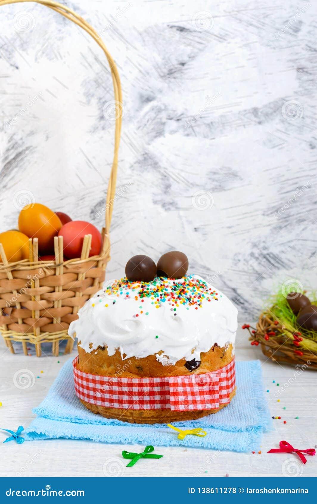 Tradycyjny wielkanoc tort kulich, czekoladowi jajka w gniazdeczku i kolorowi malujący jajka na drewnianym białym tle -,