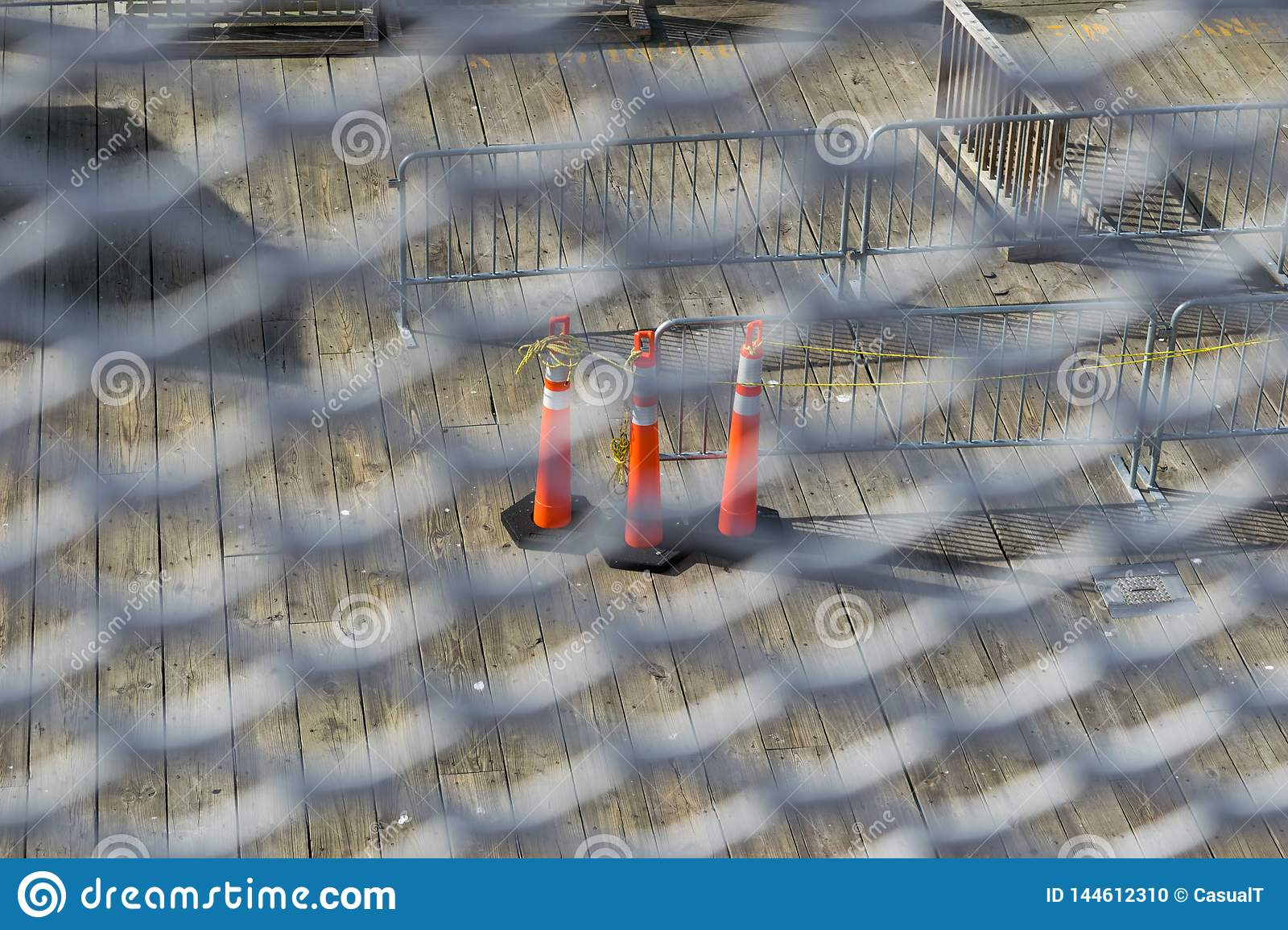 Traffic cones on a slated wooden floor, seen through a white metal grid