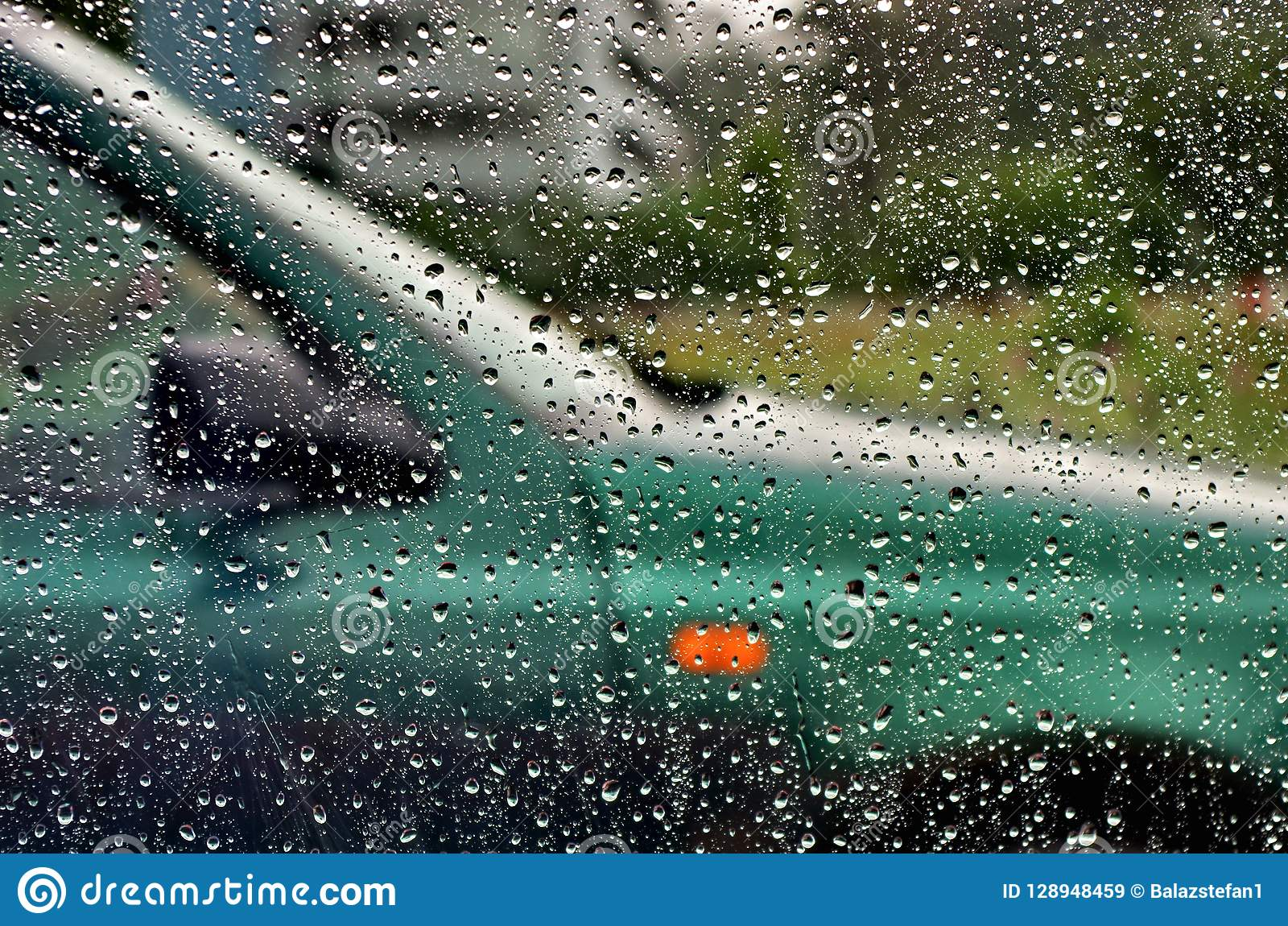 Traffic In Rainy Day With View Through Car Window With Rain