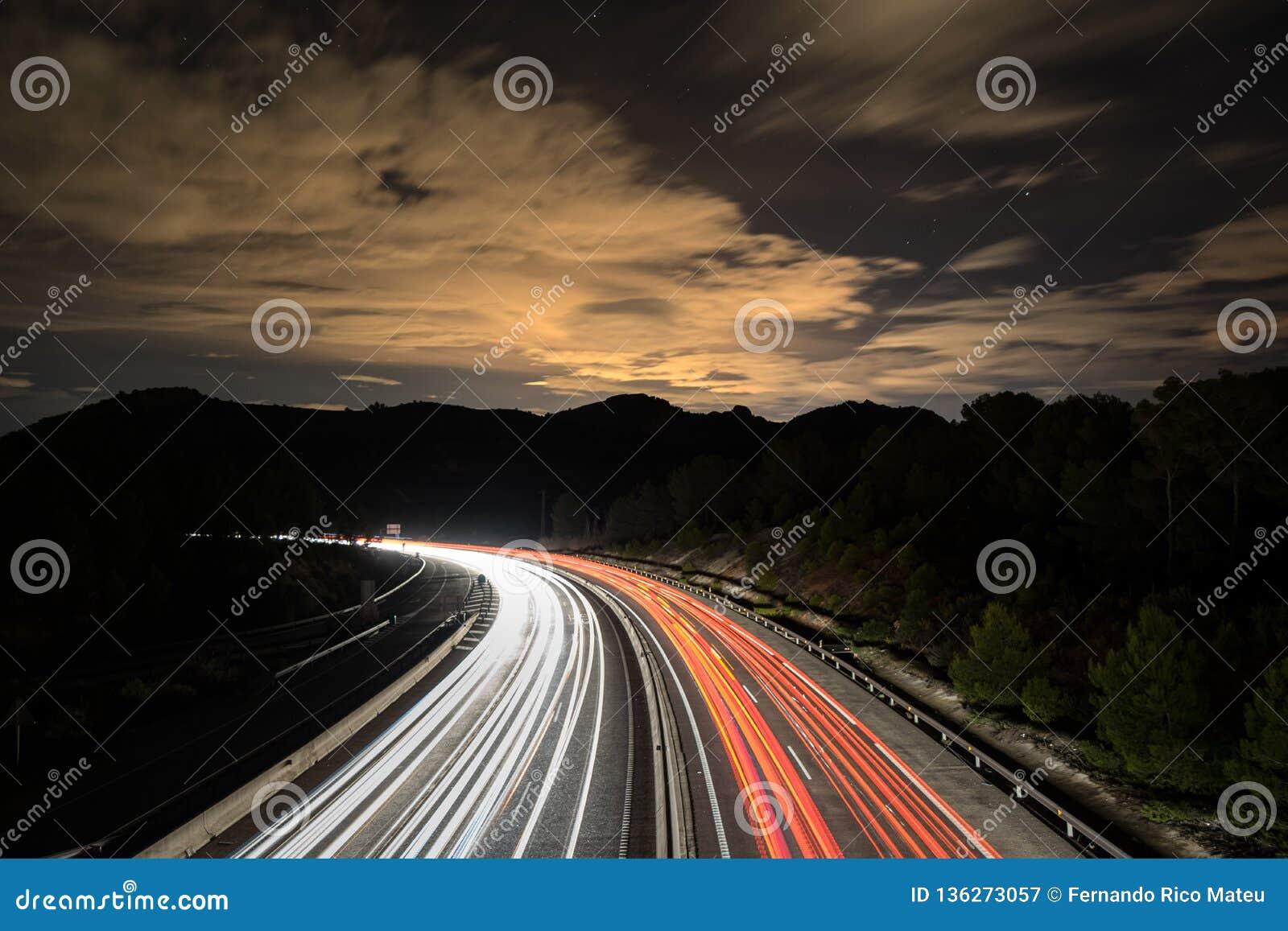 Traffico alla notte nella montagna bello nightscape Colpo lungo di esposizione