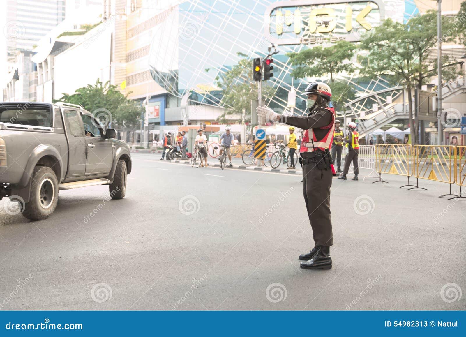 Trafikpolisen omdirigerar bilen ut ur den Pathumwan genomskärningen