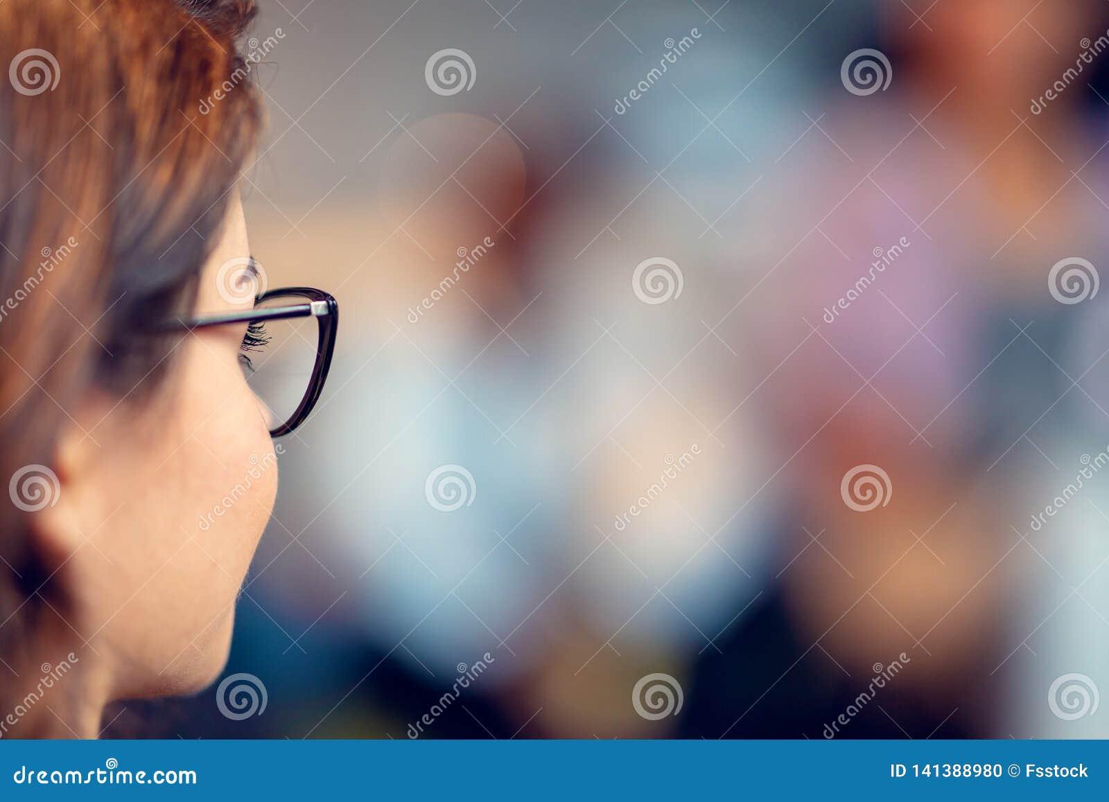 Tragende Gläser der jungen Geschäftsfrau, die sicher bei der Stellung in einem Büro mit den Kollegen arbeiten in lächeln