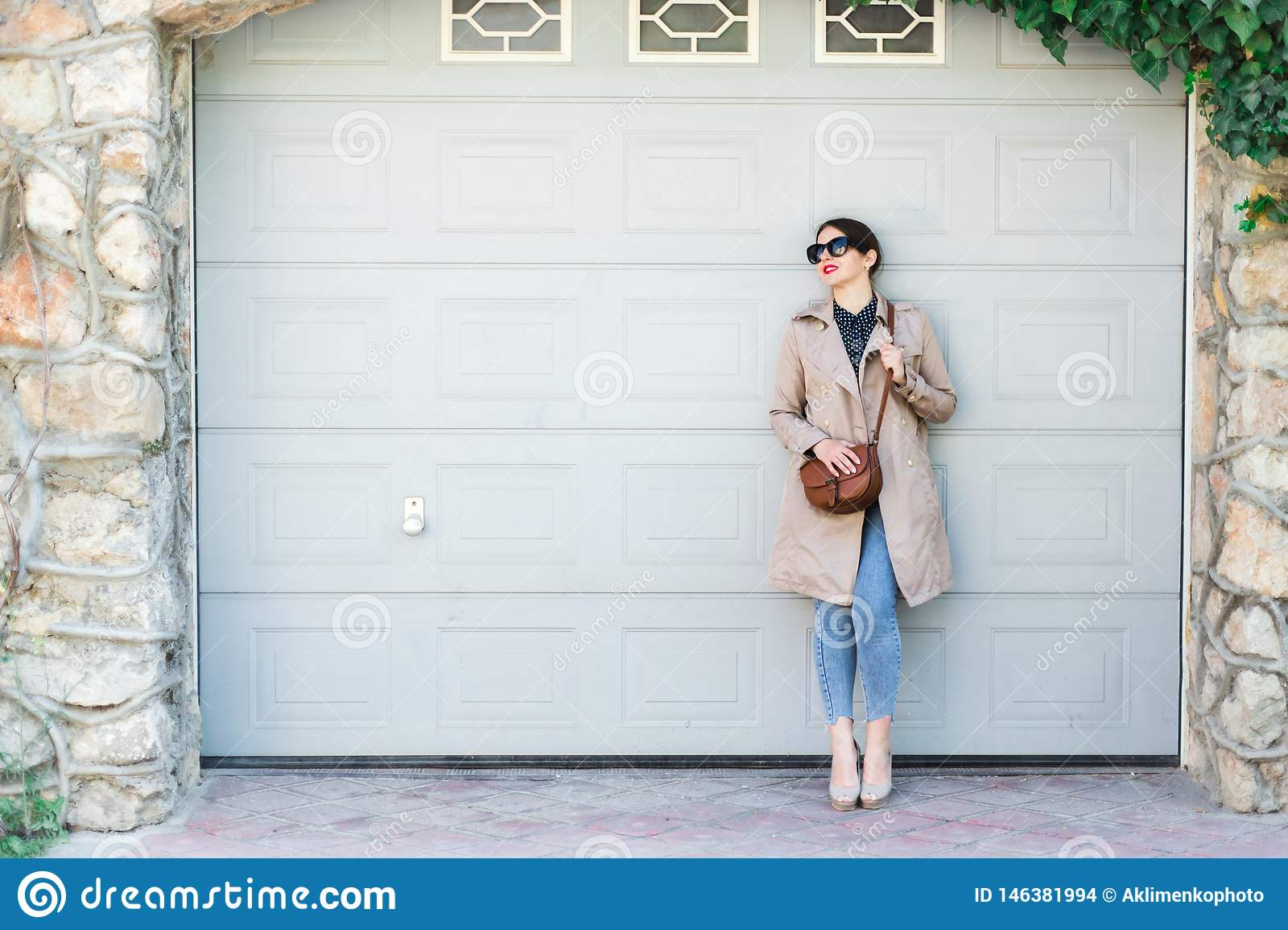 Tragende Jeans und Graben der Schönheit, stehend gegen Wand auf Stadtstraße Zuf?llige Mode, eleganter t?glicher Blick