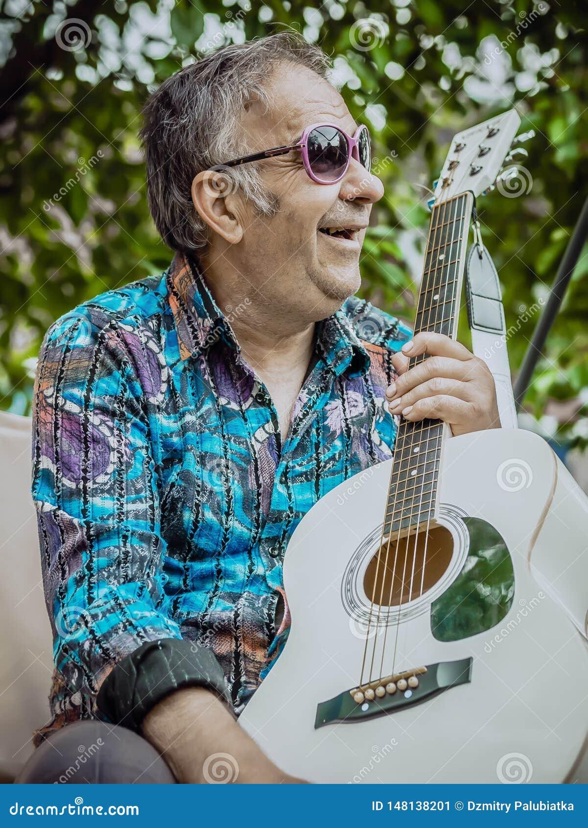 Tragende Sonnenbrille Hippie-Sankt mit einer Gitarre