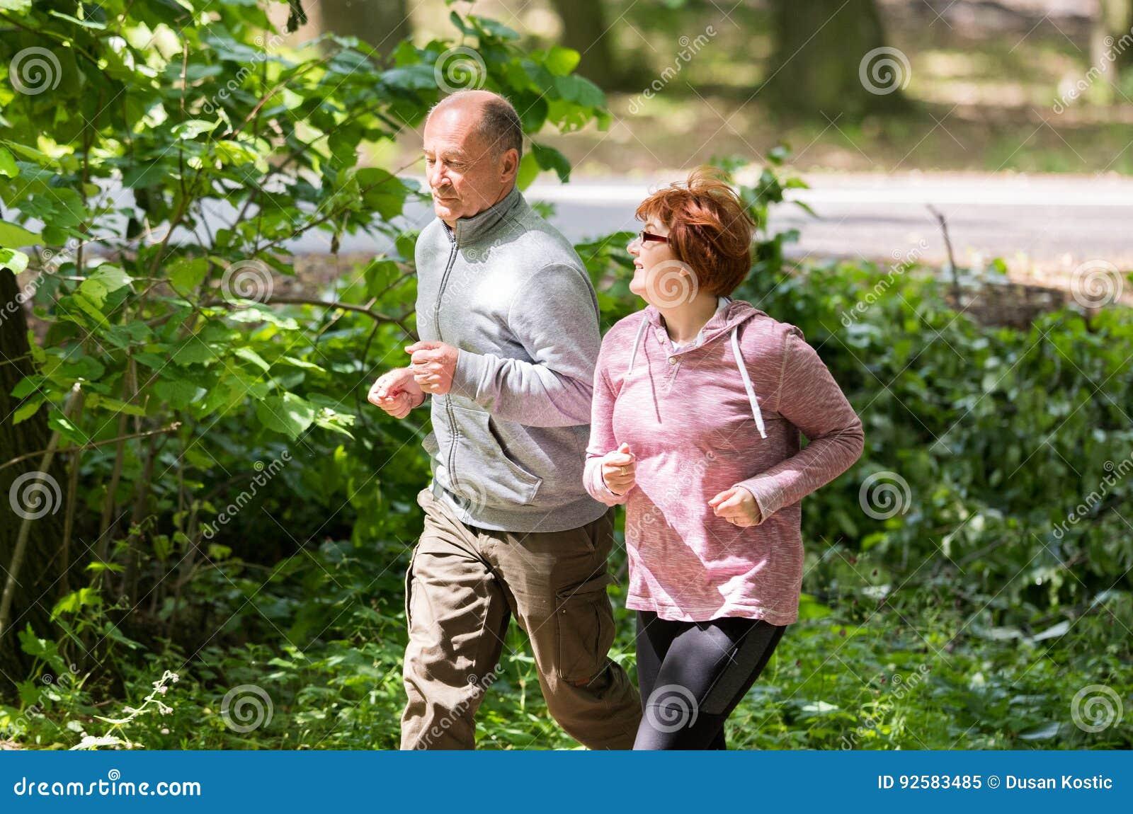 Tragende Sportkleidung und Betrieb der älteren Paare im Wald am mountai