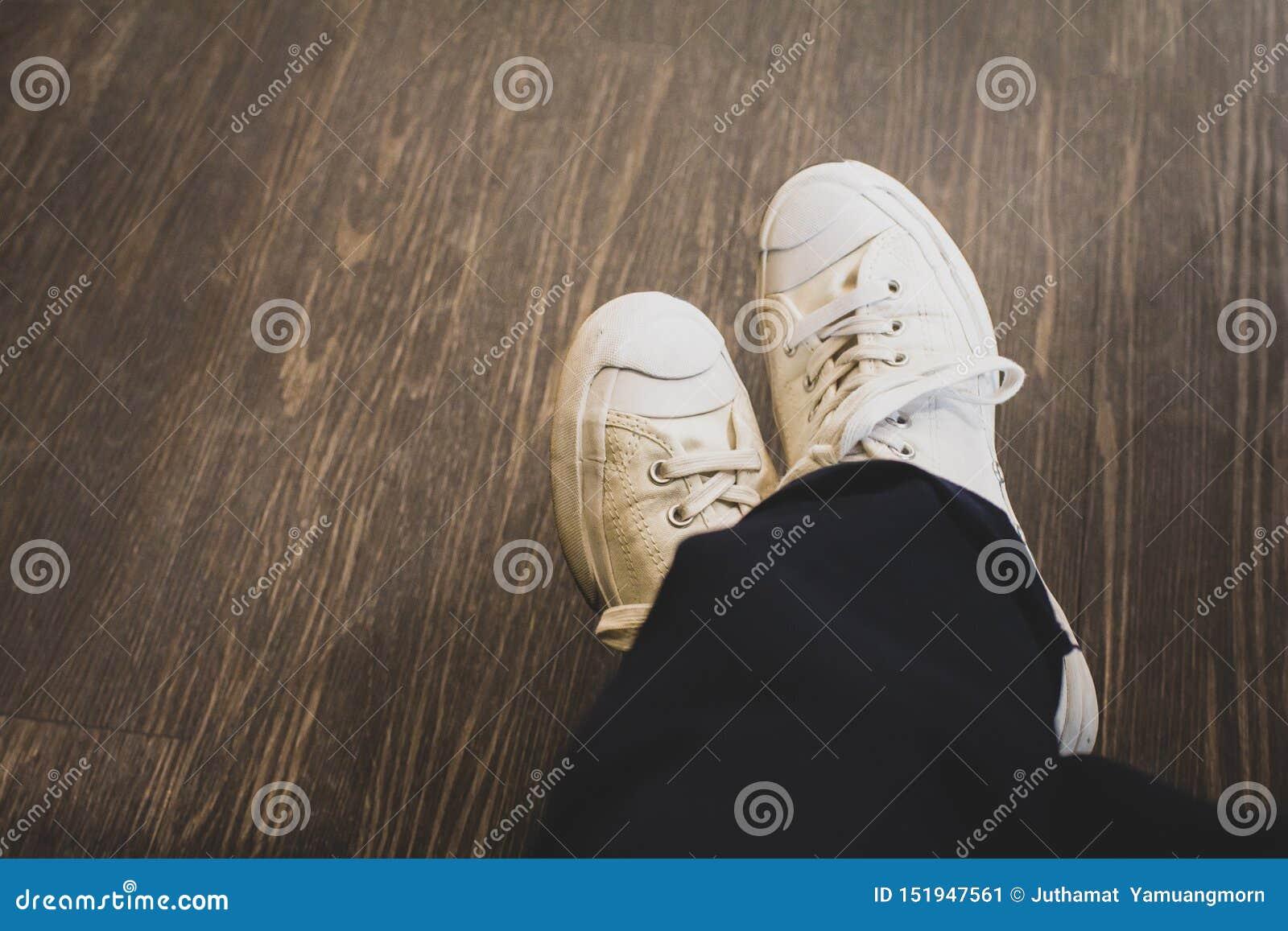 Tragende weiße Turnschuhe des Mannes in der schwarzen Hose, die auf Kaffeestube sitzt