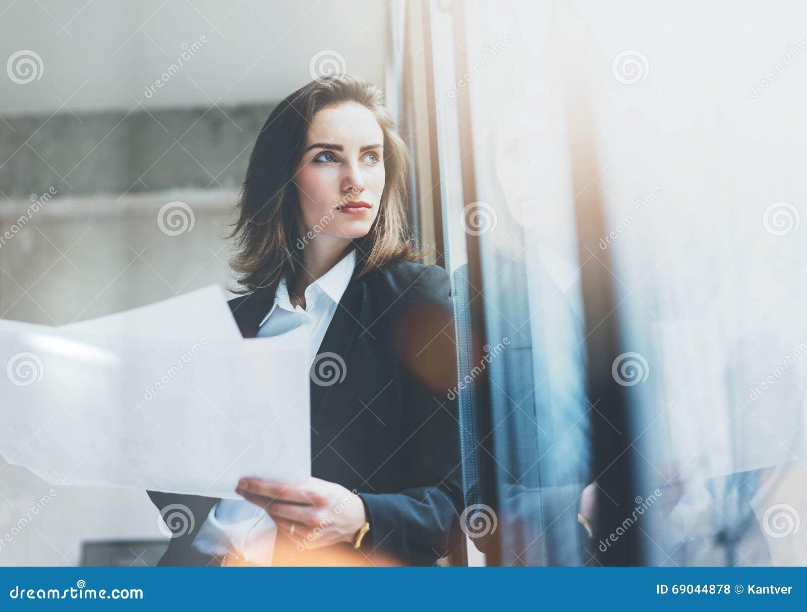 Tragender Anzug der Porträtgeschäftsfrau, Unterhaltungssmartphone und halten Papiere in den Händen Dachbodenbüro des offenen Raum