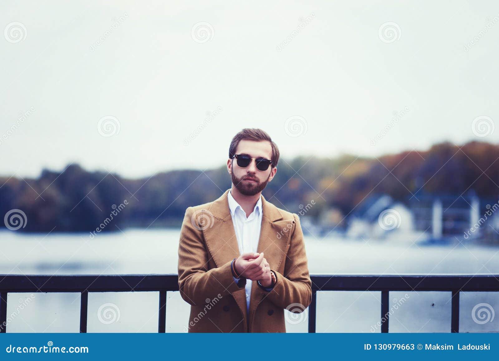 Tragender Mantel und Sonnenbrille des Mannes