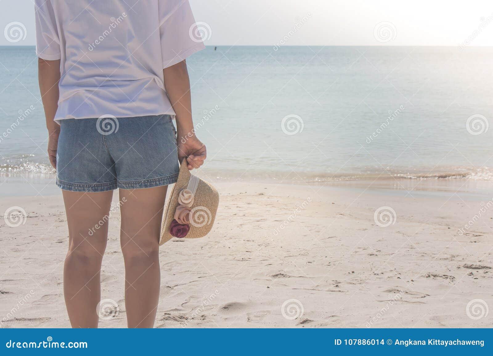 Tragendes weißes T-Shirt der Frau, sie stehend auf Sandstrand und Webarthut in der Hand halten, sie das Meer betrachtend
