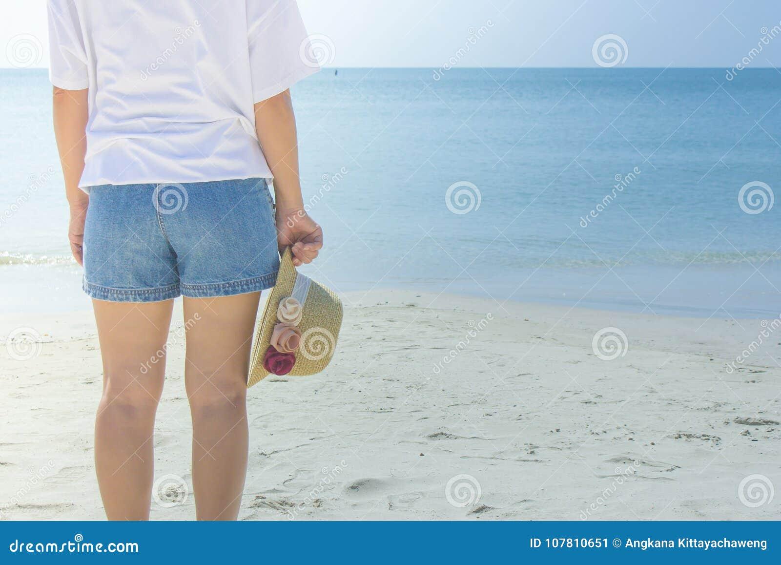 Tragendes weißes T-Shirt der Frau, sie stehend auf Sandstrand und Webarthut in der Hand halten, sie das Meer und den blauen Himme