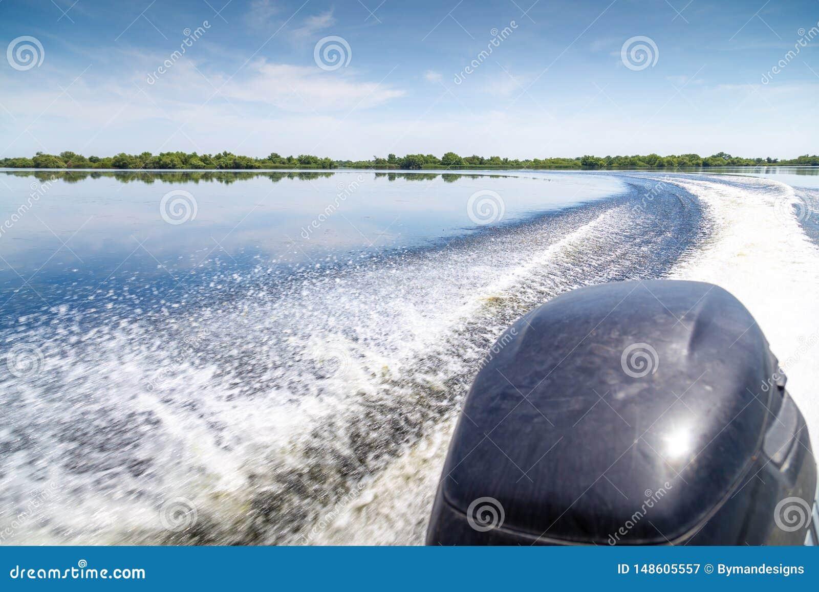 Trail of beautiful water from motor boat in Danube Delta, Romania