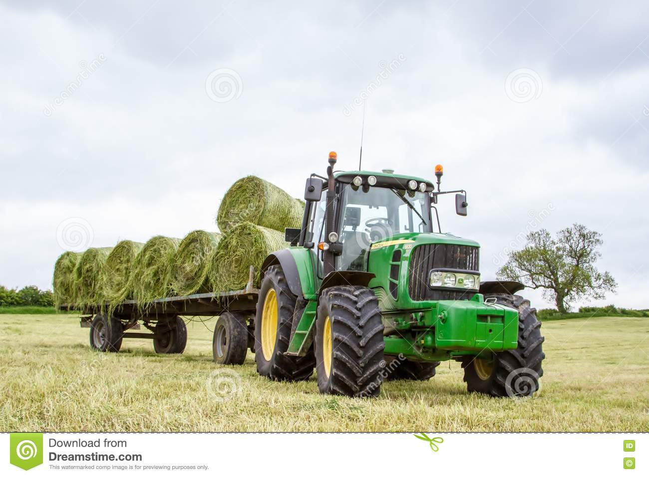Up The Tractor Green Tractor With Bucket Cartoon : Hay bales on a trailer royalty free stock photography