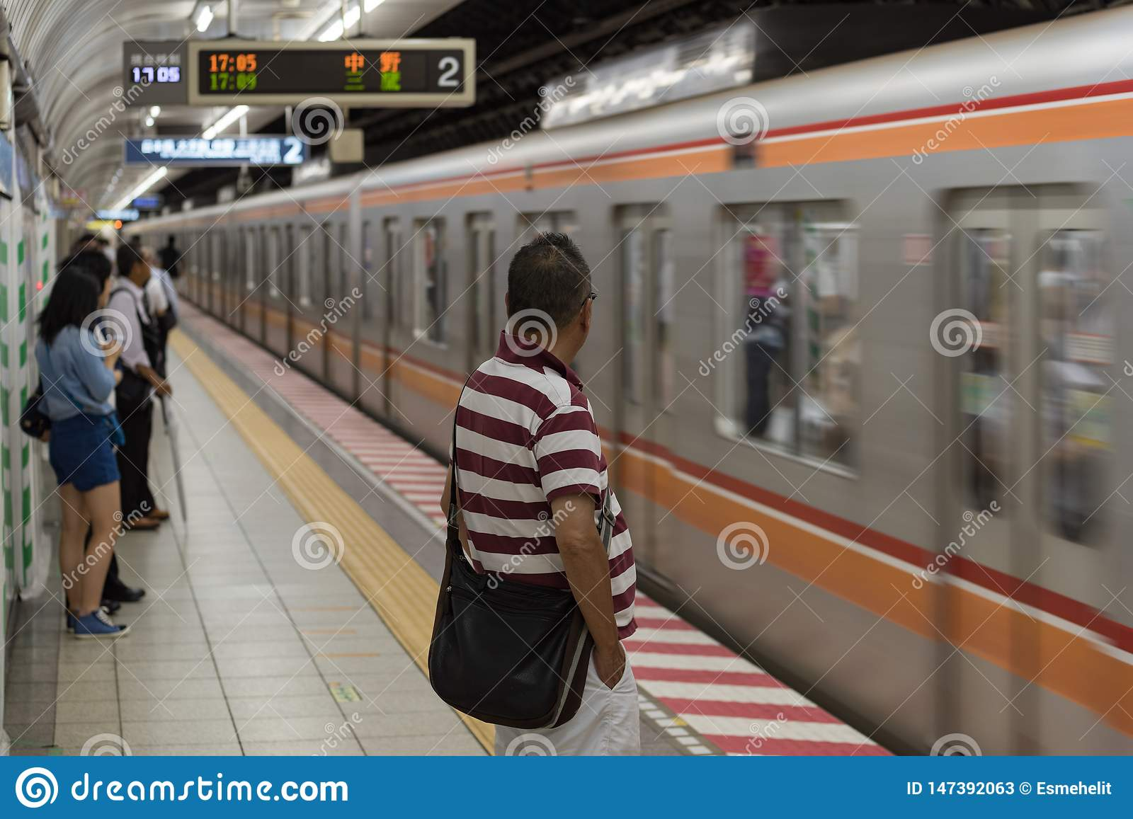 Train arriving at Tokyo Metro station with people waiting on the platform