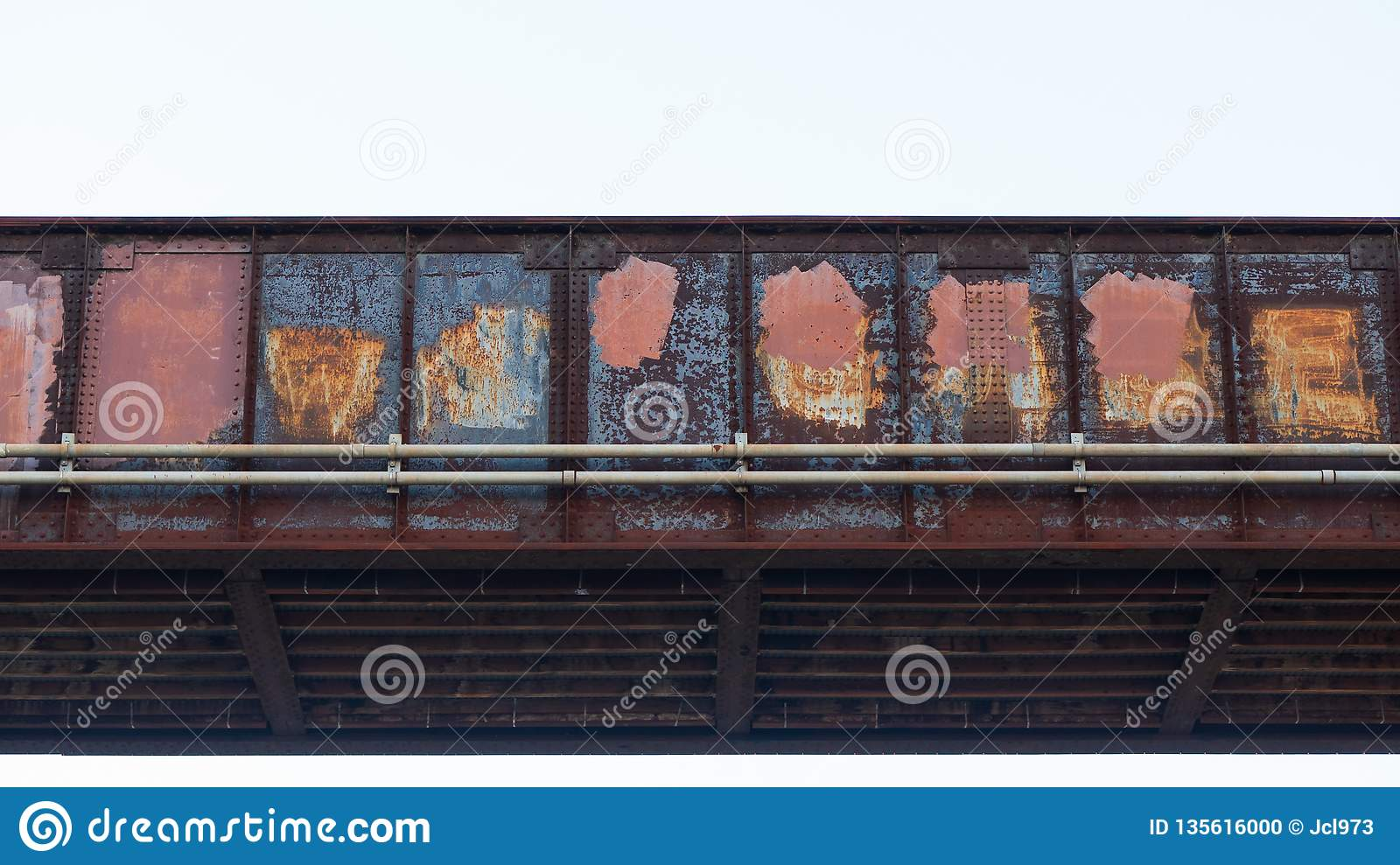Train bridge made of iron red with rust and covered in paint covering up graffiti