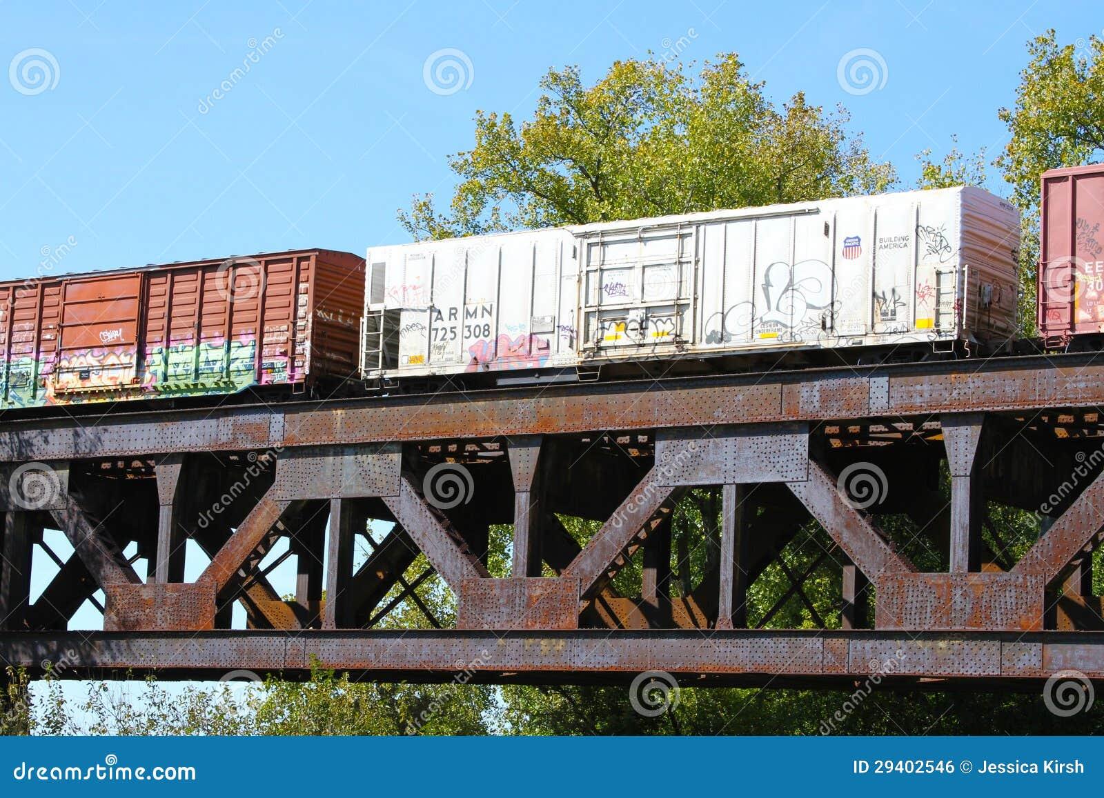 Train de fret croisant un pont en acier de rivière de botte de chemin de fer