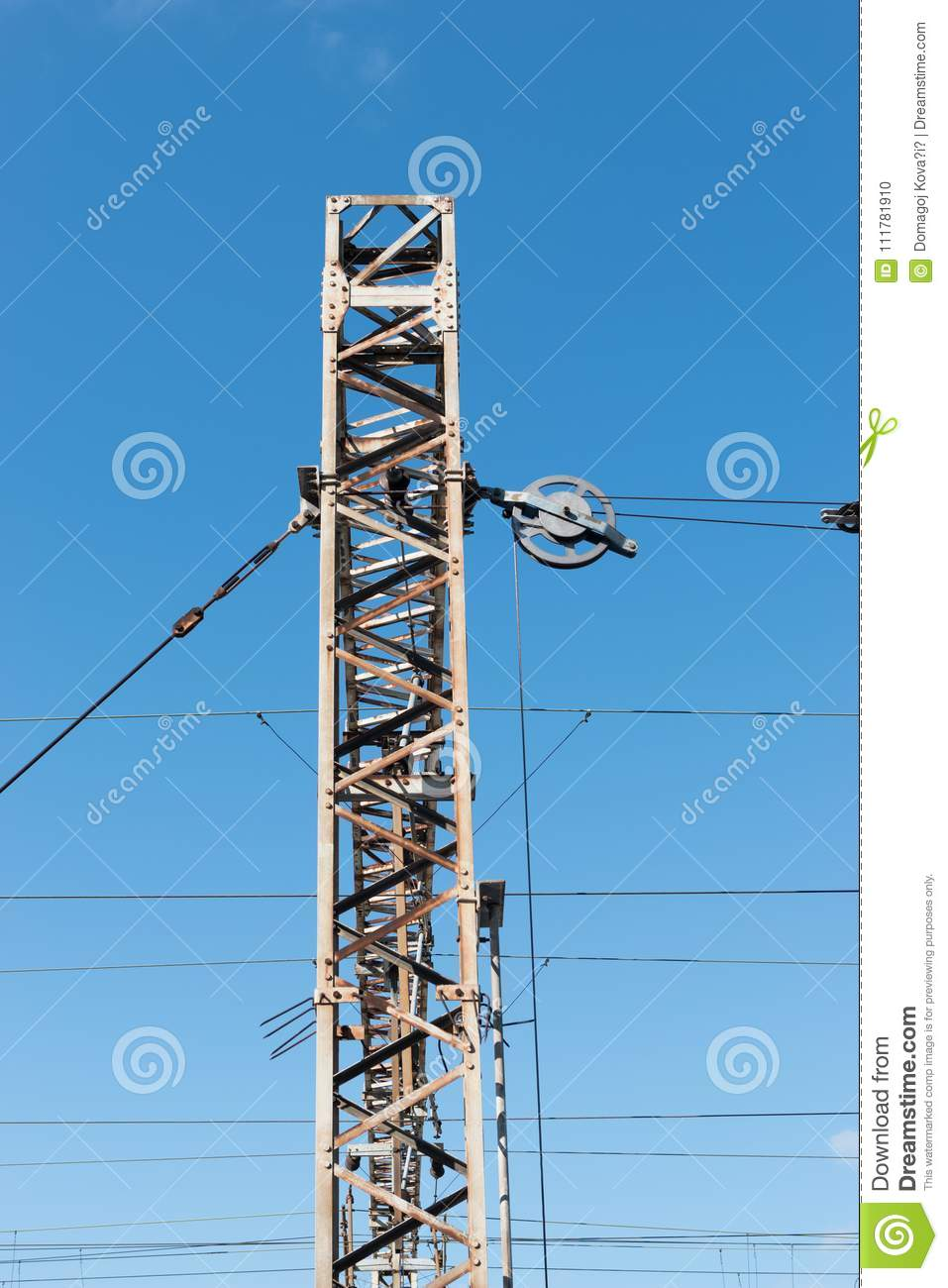 Train or railway power line support. Railway power lines with high voltage electricity on metal poles against blue sky.