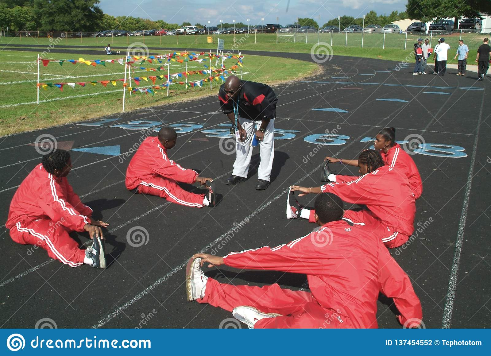 Trainer, der mit dem Bahnteam während thwy Aufwärmen mit exercisesq spricht