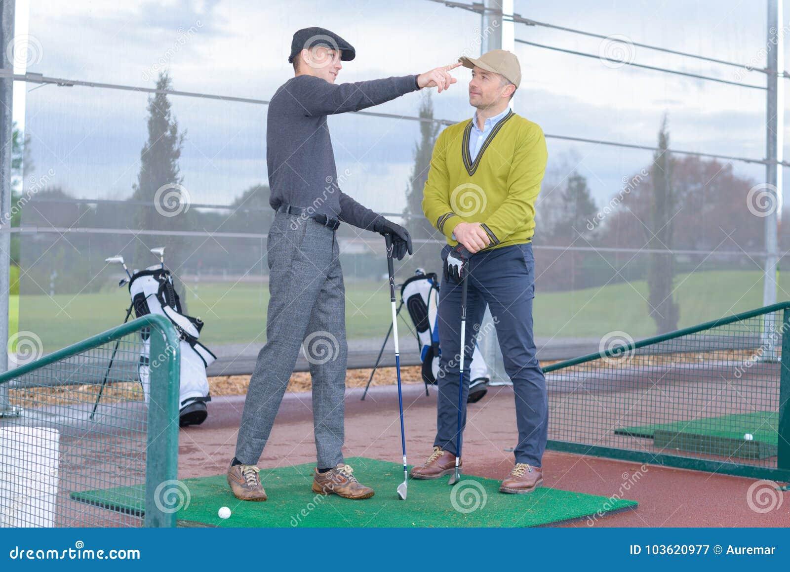 Trainer guiding novice golfer