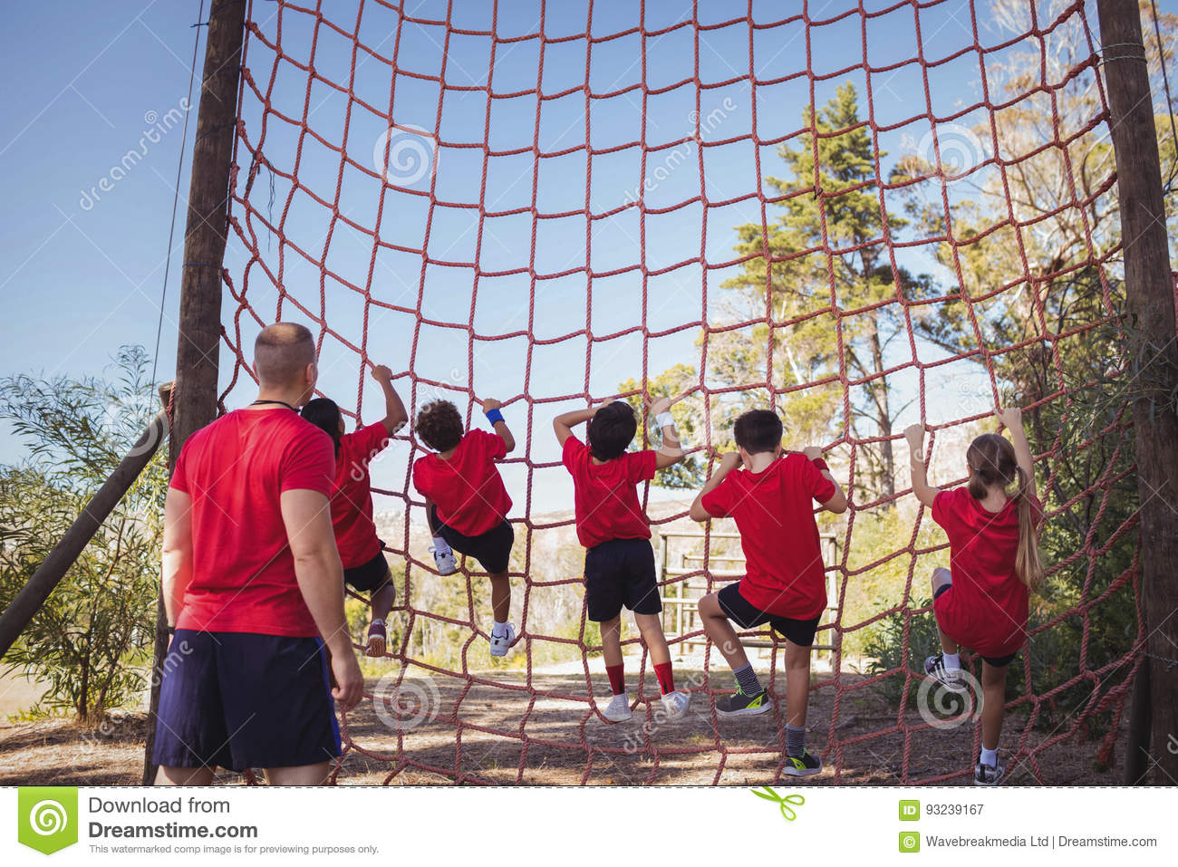 trainer instructing kids in net climbing during obstacle course