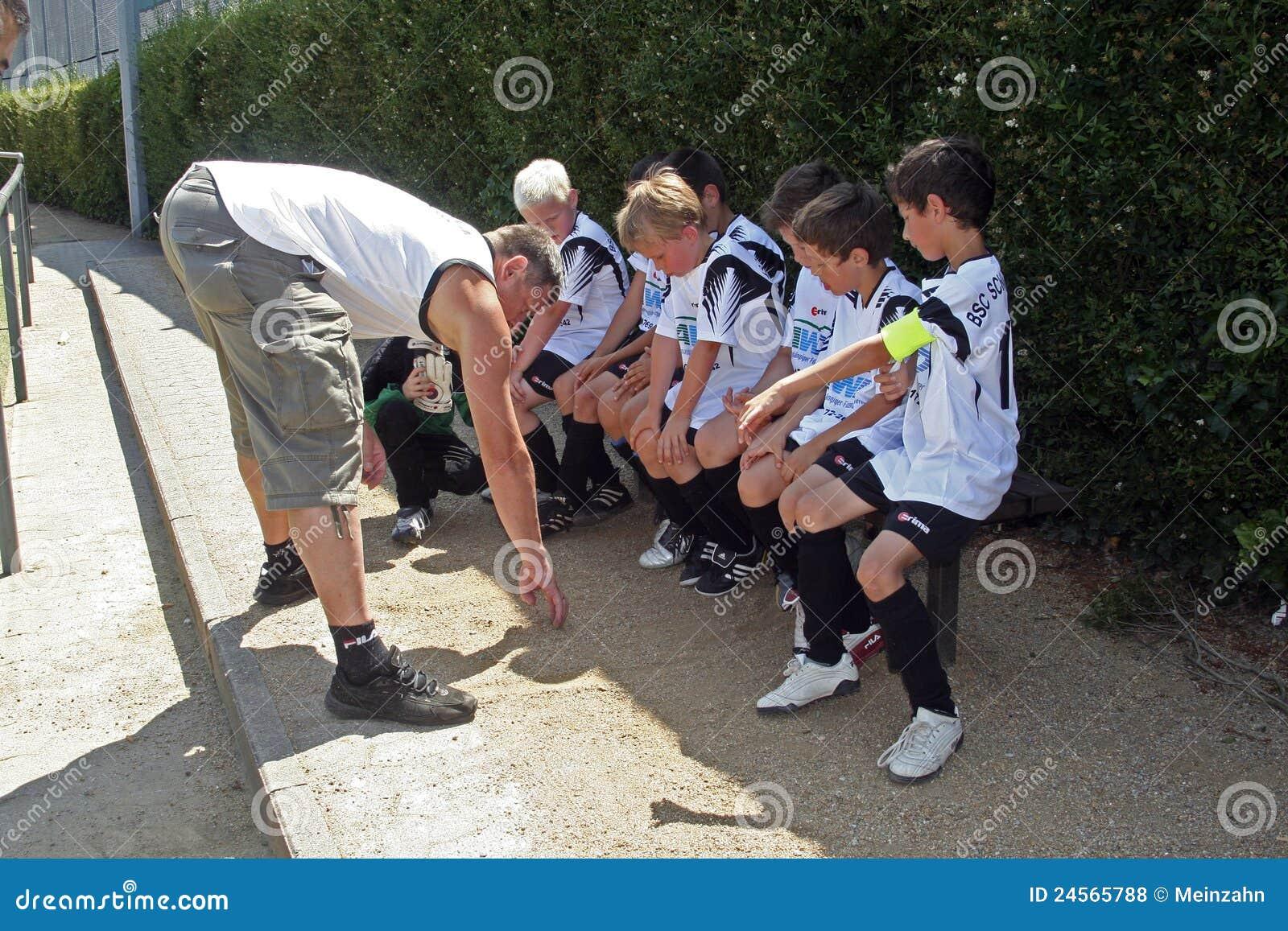 Trainer teaching children soccer