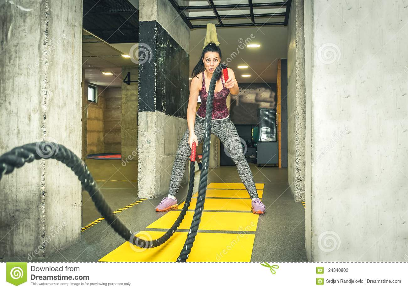 Training of beautiful young and attractive girl making fun and funny faces while she workout on the battle ropes in the gym