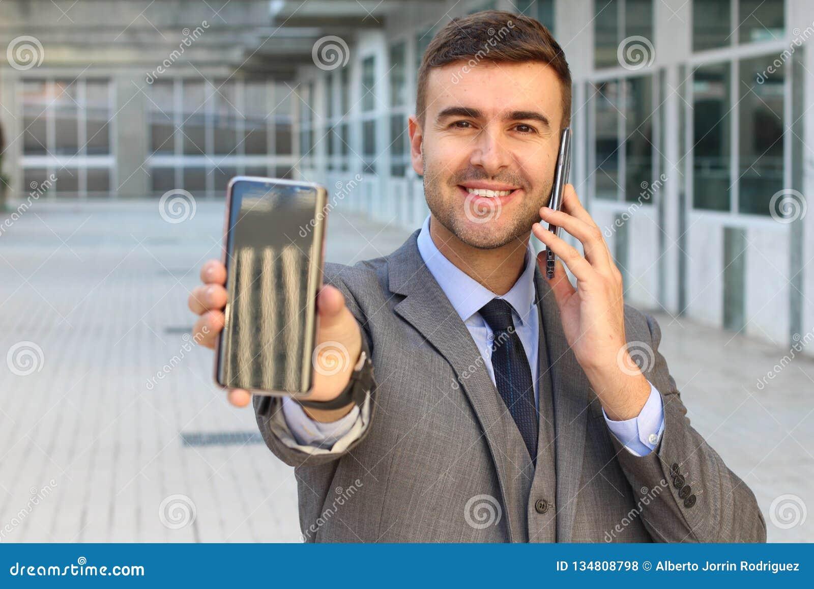 Traitement multitâche agité d homme d affaires avec deux smartphones