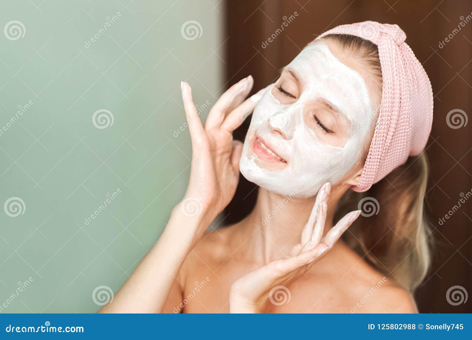 Traitements de beauté La jeune femme applique un masque, crème sur son plan rapproché de visage Portrait facial de soins de la pe