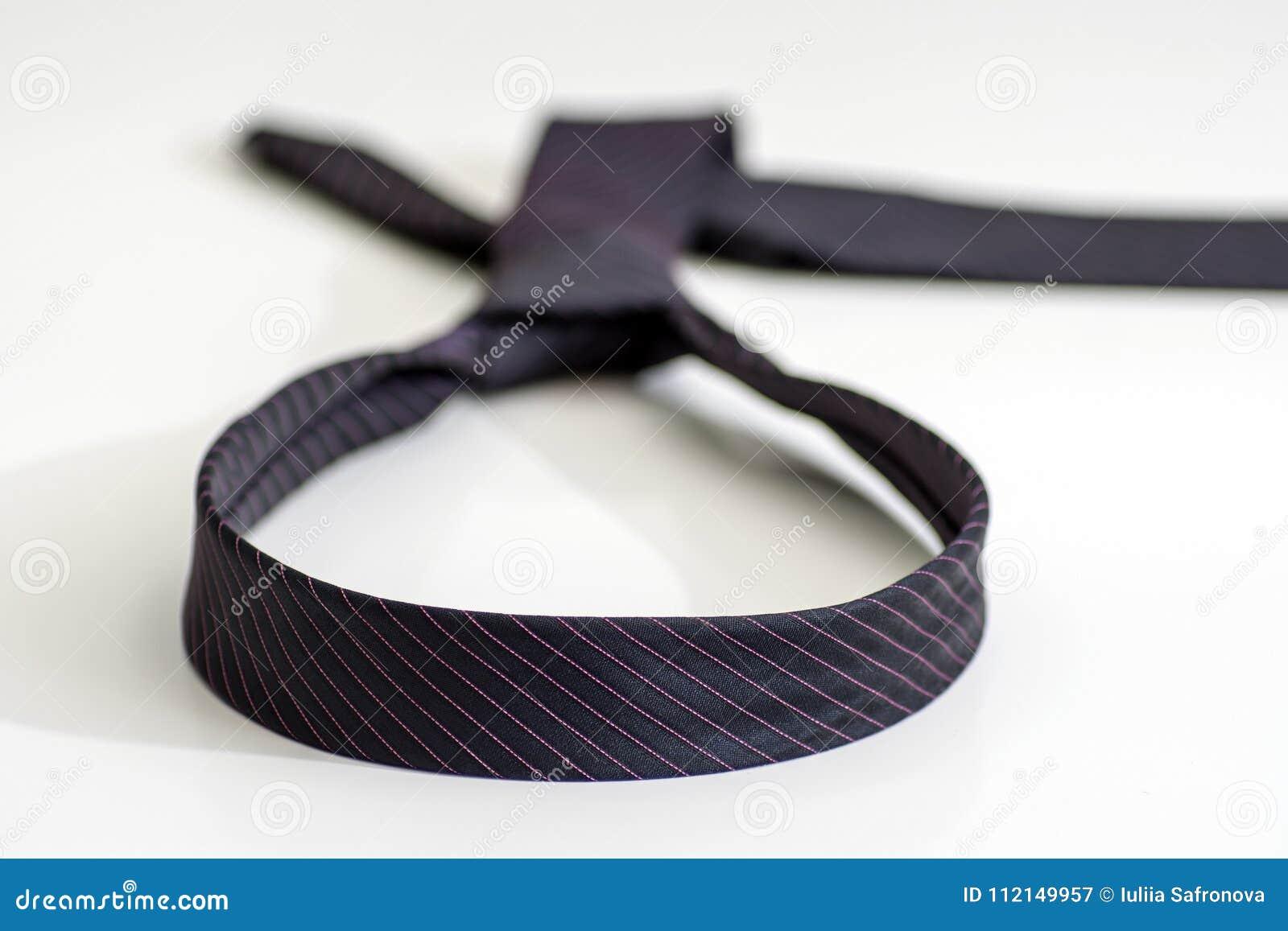 Traje de cerimônia atado em uma forma do laço em um fundo branco O engodo