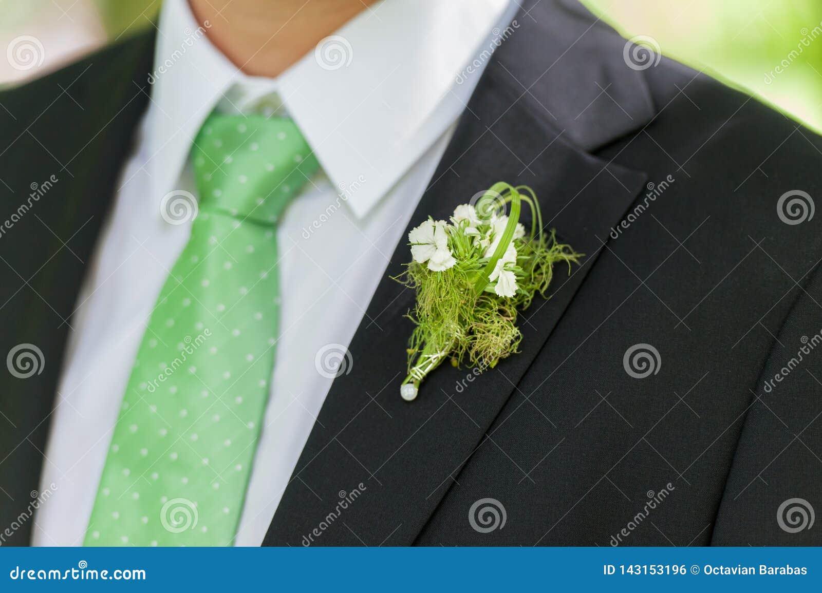 Traje del negro del novio con la decoración de la flor