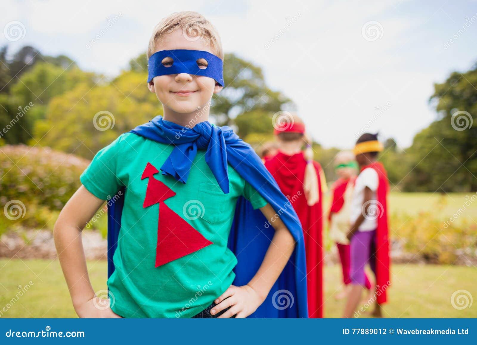 Traje Del Super Héroe Del Niño Pequeño Que Lleva Que Presenta Para La Cámara Foto de archivo