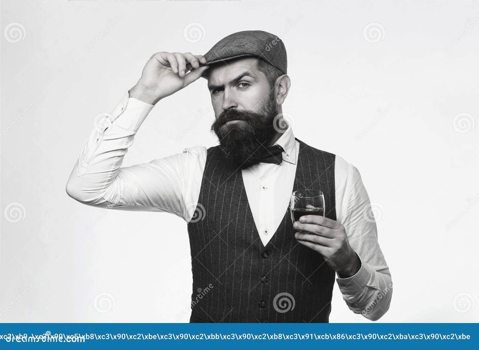 Traje que lleva y whisky de consumición, brandy, coñac del hombre barbudo Barbudo y vidrio de whisky El Sommelier prueba costoso