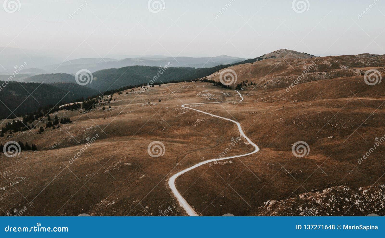 Trajeto através do vale na parte superior da corrente de montanha recolhida o por do sol jpg