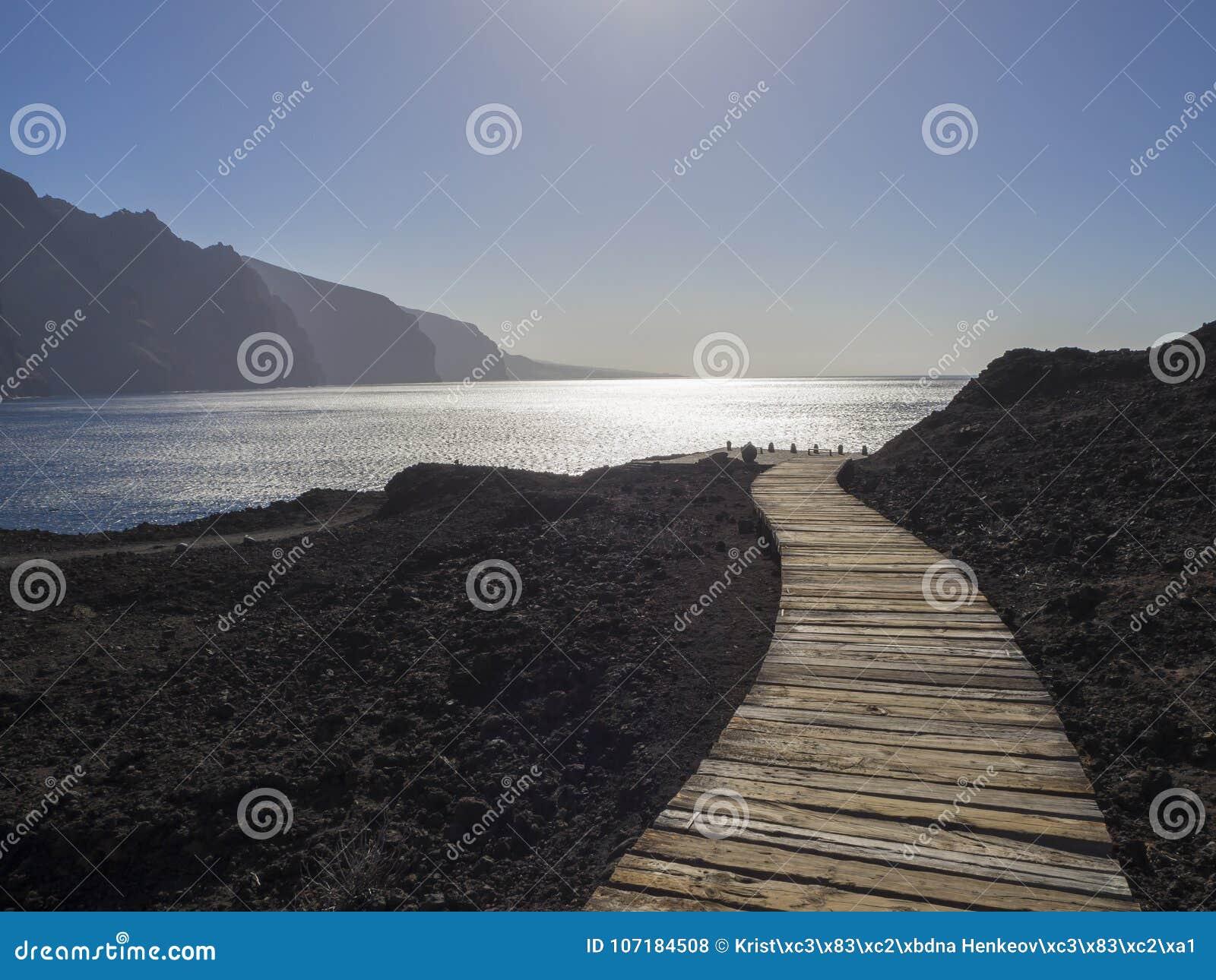 Trajeto de madeira das pranchas que conduz à costa de mar com vista na altura l