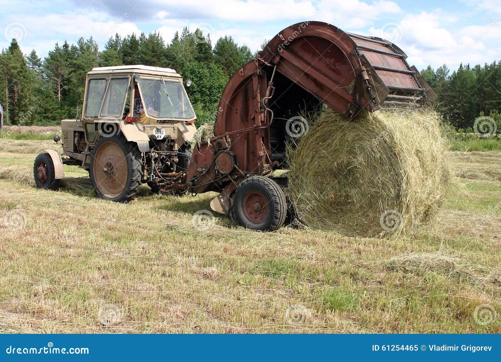 Traktor Mit Rundballenpresse Sammelt Das Heu Zum Hayfield ...