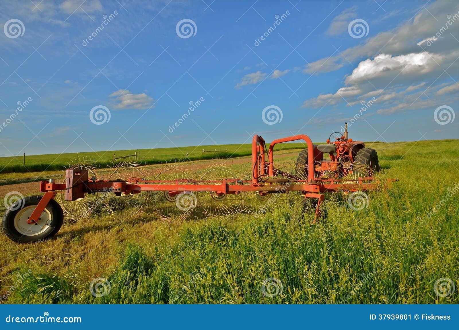 Traktoren och krattar parkerat i Hay Field