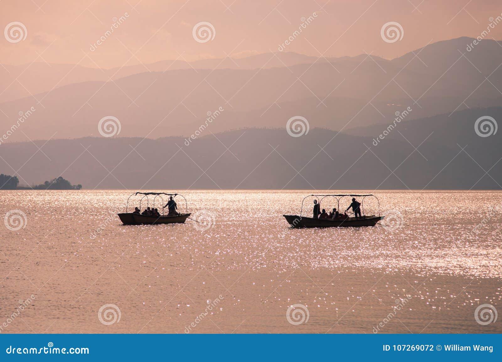Tramonto con 2 navi nel lago Qionghai in Sichuan della Cina