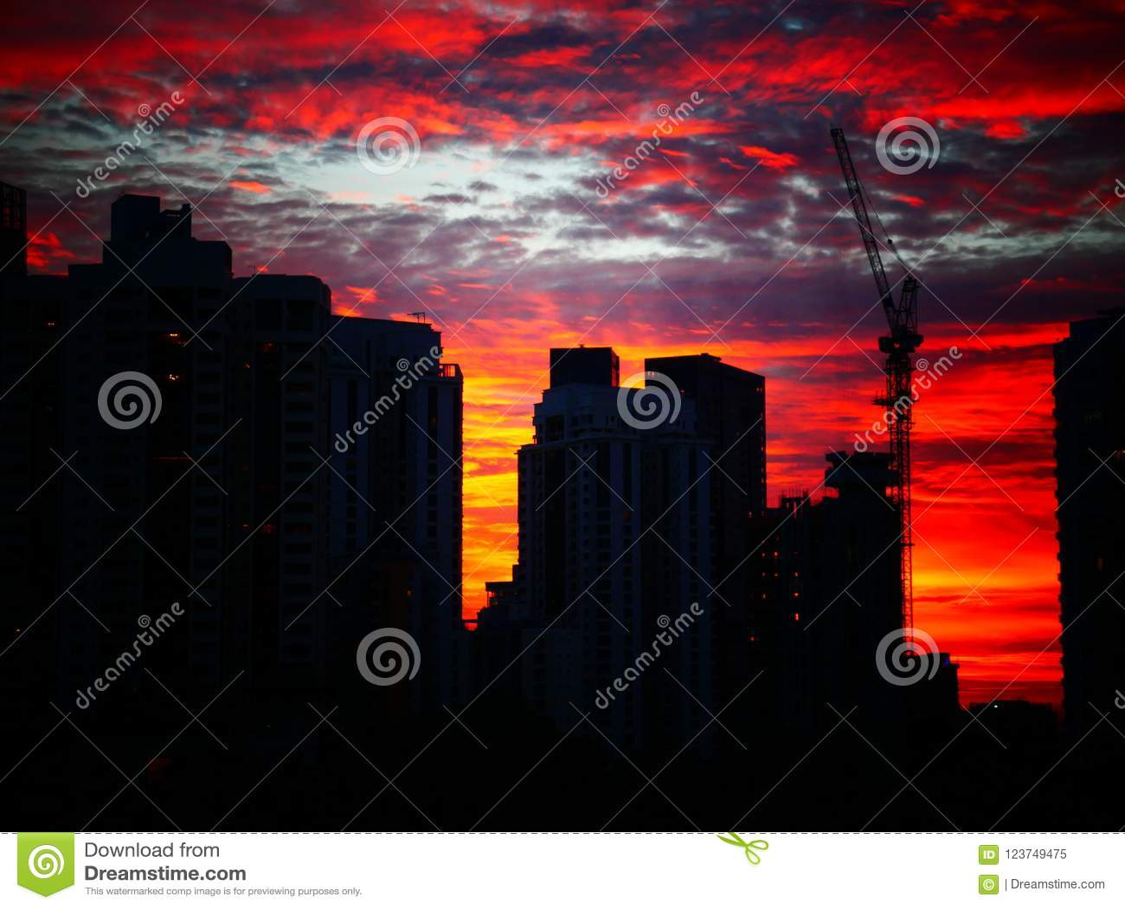 Tramonto dietro le costruzioni con il bello cielo nuvoloso