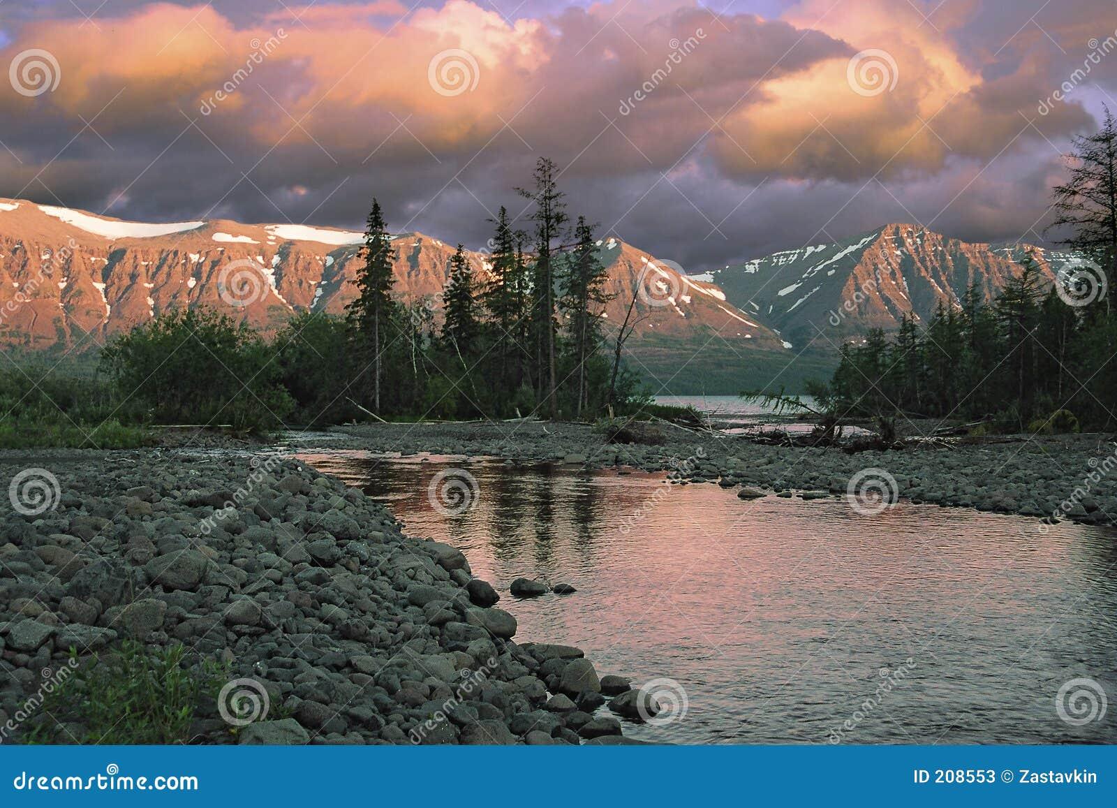 Tramonto sopra il fiume e le montagne
