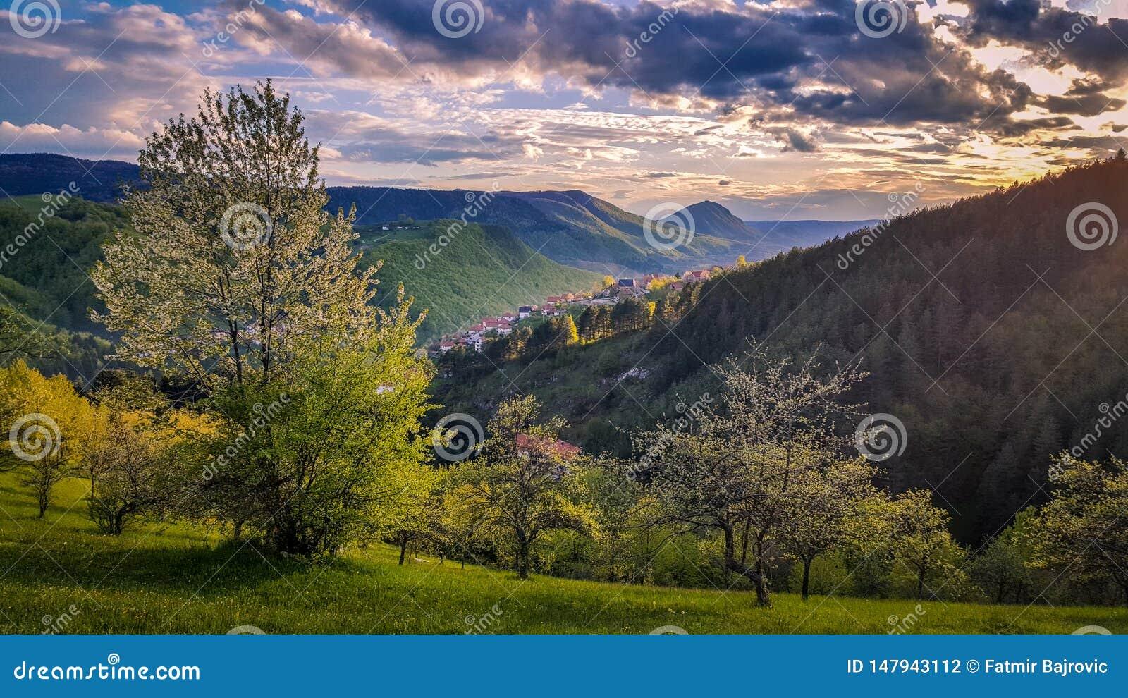 Tramonto stupefacente Vista dei paesaggi della molla, della luce solare e delle nuvole scure qui sopra