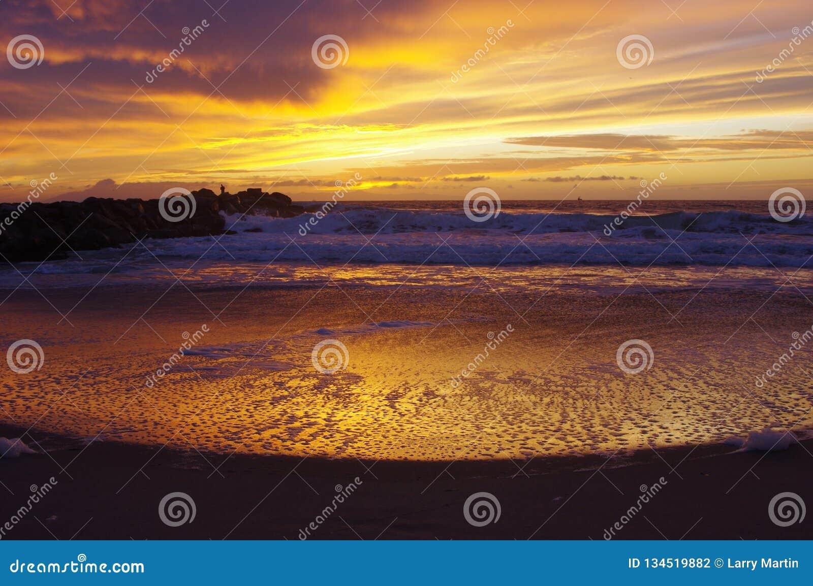 Tramonto sull oceano, sulla spuma e sulla sabbia